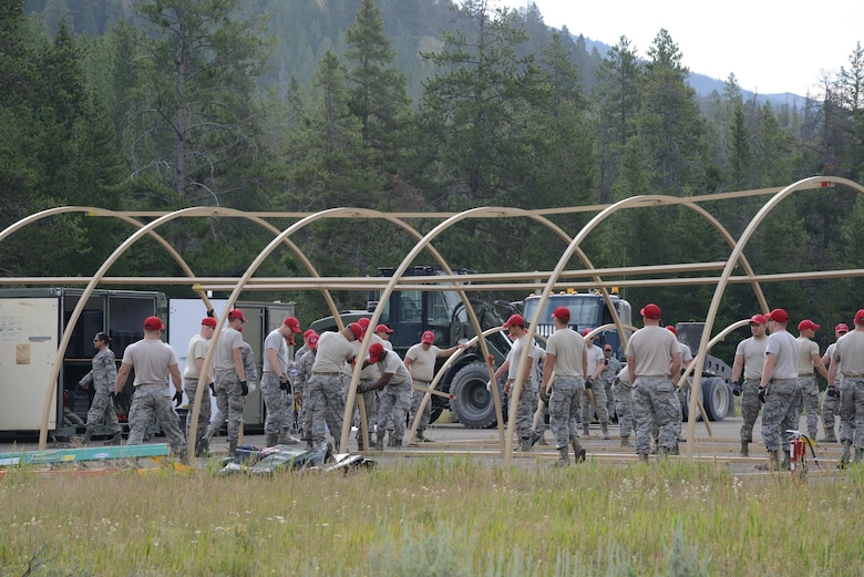 Airmen from the 819th RED HORSE Squadron set up tent frames for two Alaskan small system shelters during an exercise July 27, 2017, at the Benchmark Airport near Augusta, Mont.