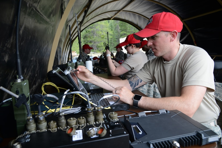 Staff Sgt. Wesley Bear, 819th RED HORSE Squadron NCO in charge of client systems, sets up communications equipment during an exercise July 27, 2017, at the Benchmark Airport near Augusta, Mont.