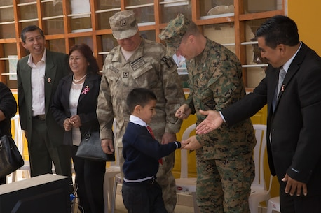 A young Peruvian student receives a command coin from U.S. Marine Col. Paul Konopke, the commanding officer of 23rd Marine Regiment, during a community relations event in Huarmey, Peru, as part of UNITAS 2017, July 24, 2017. Much of Huarmey had been damaged by recent flooding, and Marines delivered more than 100 pallets of donated items from Project Handclasp for the city's hospital and schools. Project Handclasp is a U.S. Navy program that delivers humanitarian and educational materials donated by U.S. citizens. UNITAS is an annual, multinational exercise that focuses on strengthening existing regional partnerships and encourages establishing new relationships through the exchange of maritime mission-focused knowledge and expertise during multinational training operations. (U.S. Marine Corps photo by 1st Lt. Marco Valenzuela)