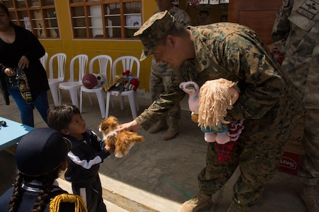 U.S. Marine Staff Sgt. Emanuel Chico, a platoon commander with Lima Company, 3rd Battalion, 23rd Marine Regiment, hands donated toys to a young Peruvian student during a community relations event in Huarmey, Peru, as part of UNITAS 2017, July 24, 2017. Much of Huarmey had been damaged by recent flooding, and Marines delivered more than 100 pallets of donated items from Project Handclasp for the city's hospital and schools. Project Handclasp is a U.S. Navy program that delivers humanitarian and educational materials donated by U.S. citizens. UNITAS is an annual, multinational exercise that focuses on strengthening existing regional partnerships and encourages establishing new relationships through the exchange of maritime mission-focused knowledge and expertise during multinational training operations. (U.S. Marine Corps photo by 1st Lt. Marco Valenzuela)