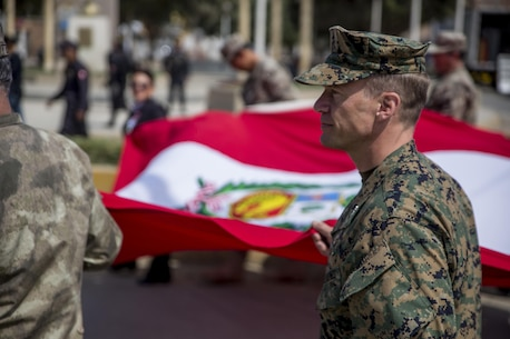 U.S. Marine Col. Paul Konopka holds on to the Peruvian national flag during a symbolic march around the city square in Huarmey, Peru, during a community relations event as part of UNITAS 2017, July 24, 2017. Much of Huarmey had been damaged by recent flooding, and Marines delivered more than 100 pallets of donated items from Project Handclasp for the city's hospital and schools. Project Handclasp is a U.S. Navy program that delivers humanitarian and educational materials donated by U.S. citizens. UNITAS is an annual, multi-national exercise that focuses on strengthening existing regional partnerships and encourages establishing new relationships through the exchange of maritime mission-focused knowledge and expertise during multinational training operations. (U.S. Marine Corps photo by 1st Lt. Marco Valenzuela)