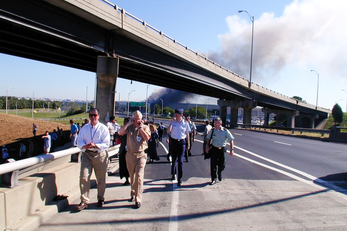 Military and civilian personnel walk down a highway after evacuating the Pentagon.