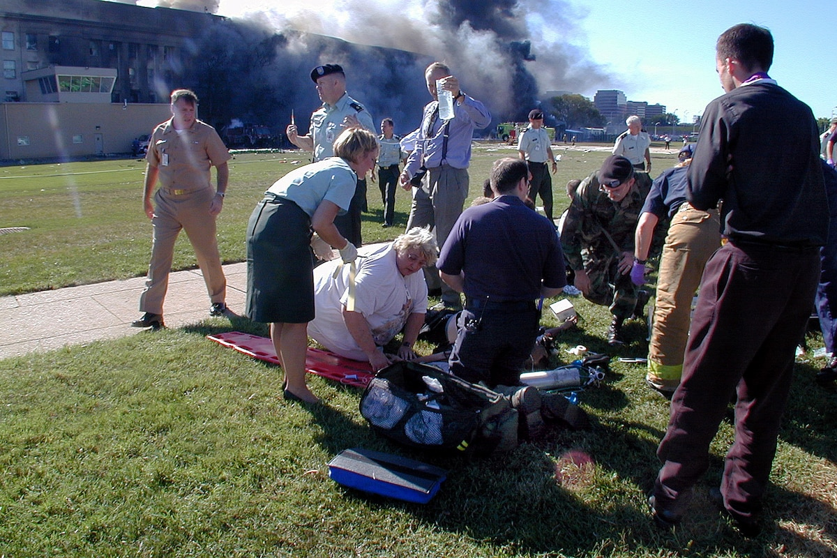 Medical personnel and volunteers work the first medical triage area outside the Pentagon after a hijacked commercial airliner crashed into the southwest corner of the building, Sept. 11, 2001. Navy photo by Petty Officer 1st Class Mark D. Faram