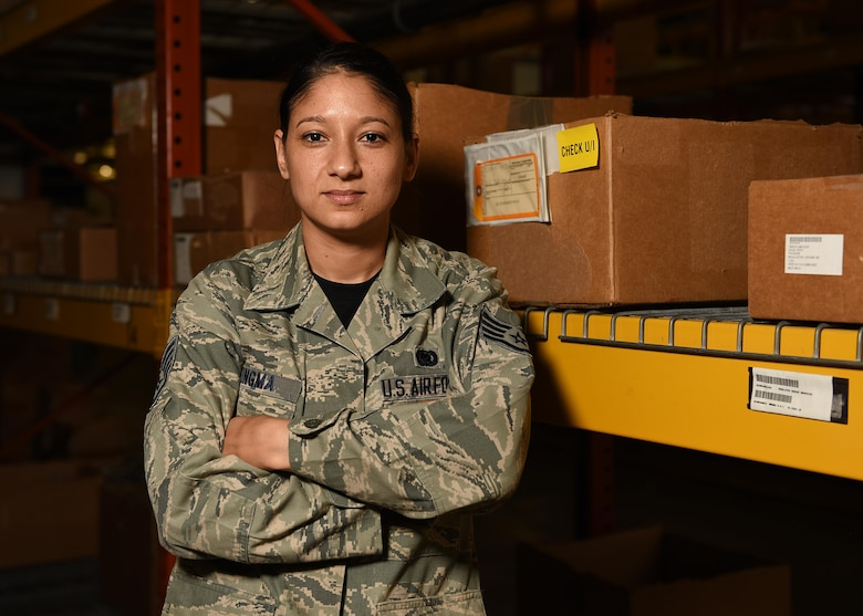 Female staff sergeant poses in front boxes with her arms crossed.