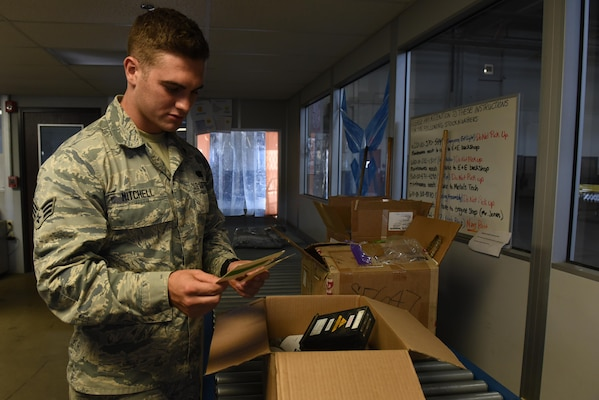 Male senior airman checks a returned item status that was on a industrial line.