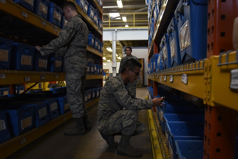 Three airmen in a warehouse search through boxes.