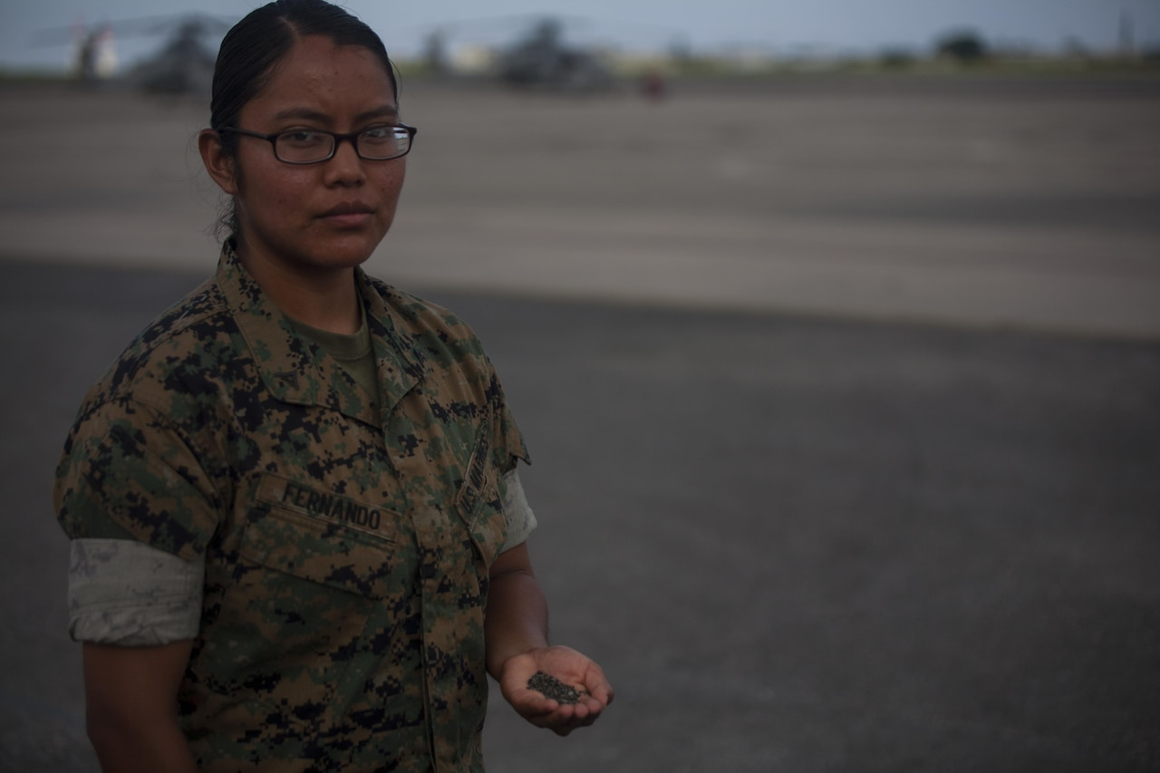 Marine Corps Lance Cpl. Jeanette E. Fernando holds a handful of sand taken from her trip to Iwo Jima, at Marine Corps Air Station Futenma, Okinawa, Japan, Aug. 1, 2017. Fernando and other Marines in her squadron revisited the battlegrounds at which Fernando's grandfather, a Navajo Code Talker, fought during World War II.
