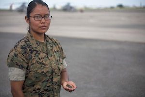 A Marine holds some sand taken from her trip to Iwo Jima.