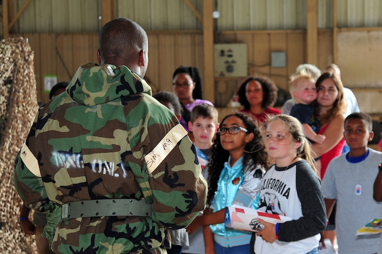 U.S. Air Force Staff Sgt. Wendell Walker, 20th Force Support Squadron (FSS) unit deployment manger, speaks to children about individual protective equipment during a Kids Meet the Shaw Weasels event at Shaw Air Force, S.C., July 28, 2017. The 20th FSS Airman and Family Readiness Center event was intended to provide children a fun and educational experience to help them understand what military members do. (U.S. Air Force photo by Airman 1st Class Kathryn R.C. Reaves)