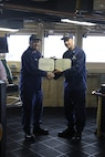 CAPT Tlapa congratulates BMCS Cichoracki as he is awarded the Coast Guard Commendation Medal.