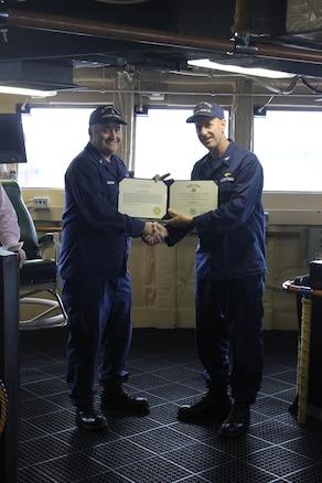 CAPT Tlapa congratulates BMCS Cichoracki as he is awarded the Coast Guard Commendation Medal.