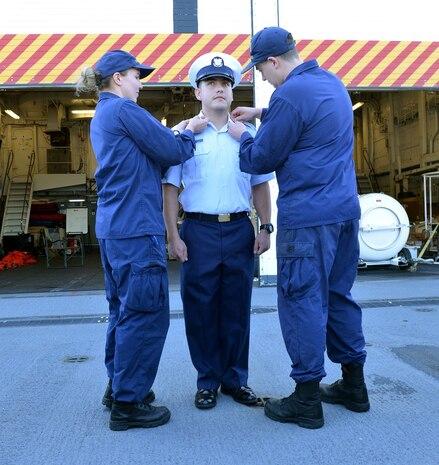 CS1 Densmore and CS3 Jackson present CS3 Taylor his new rank insignia, Petty Officer Third Class.