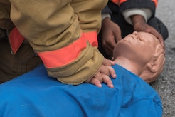 Fire Explorer Academy cadet performs CPR on a training dummy during an exercise.