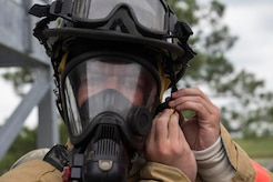 Fire Explorer Academy cadet Trevette Kuester dons his helmet during an exercise