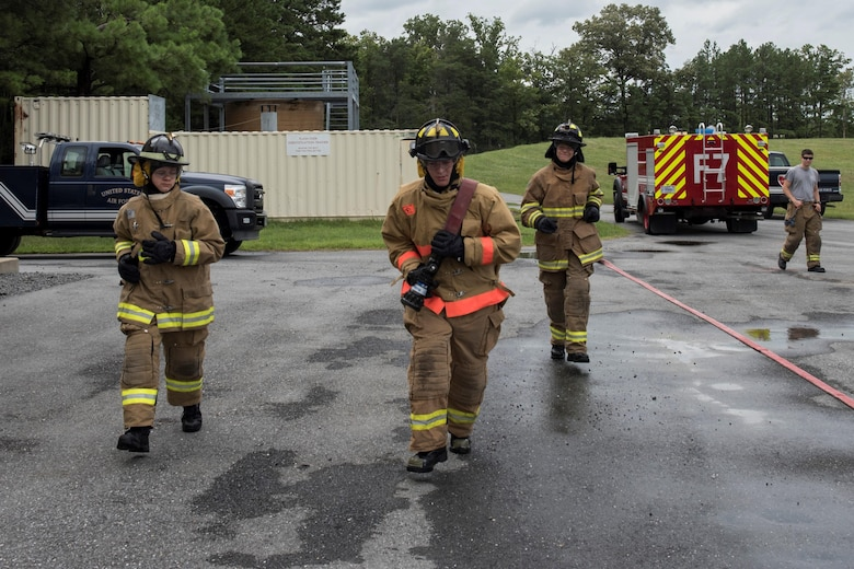 Fire Explorer Academy cadet performs a hose pull during a training exercise.