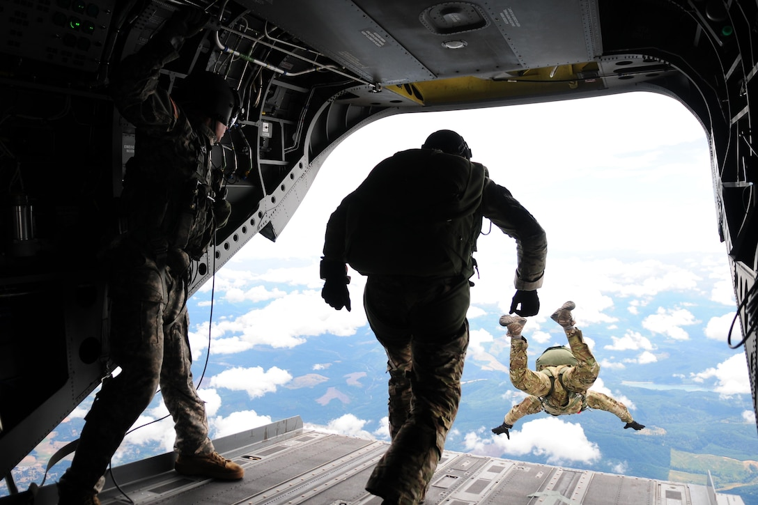 Airmen jump out of a Chinook helicopter during Operation Husky Airborne