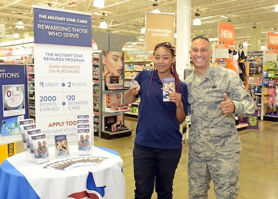 Chief Master Sgt. Luis Reyes, Army and Air Force Exchange Service's senior enlisted advisor, poses for a photo with Exchange employee Rikkie DeMary after Reyes presented her with an AAFES coin for a job well done Aug. 1. Reyes visited the Edwards Exchange and also met with 412th Mission Support Group leadership during a two-day visit to the base. (U.S. Air Force photo by Kenji Thuloweit)