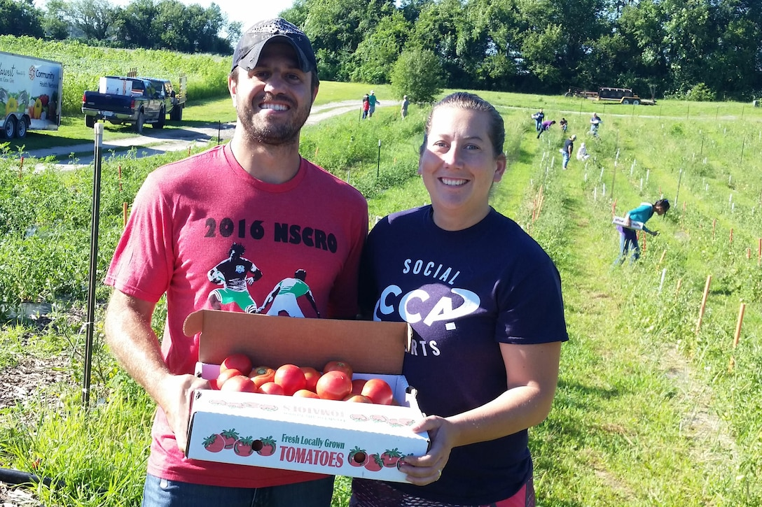 Two volunteers hold a carton of tomatoes in a field.