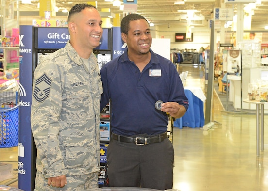 Chief Master Sgt. Luis Reyes, Army and Air Force Exchange Service's senior enlisted advisor, poses for a photo with Edwards AFB Exchange employee Jeff Thomas after Reyes presented him with an AAFES coin for a job well done Aug. 1. Reyes acts as the voice of the Exchange, traveling to military installations worldwide to meet with garrison and wing leadership, as well as customers about the Exchange and benefits to its patrons. He also brings issues back to the command to be resolved and/or implemented. (U.S. Air Force photo by Kenji Thuloweit)