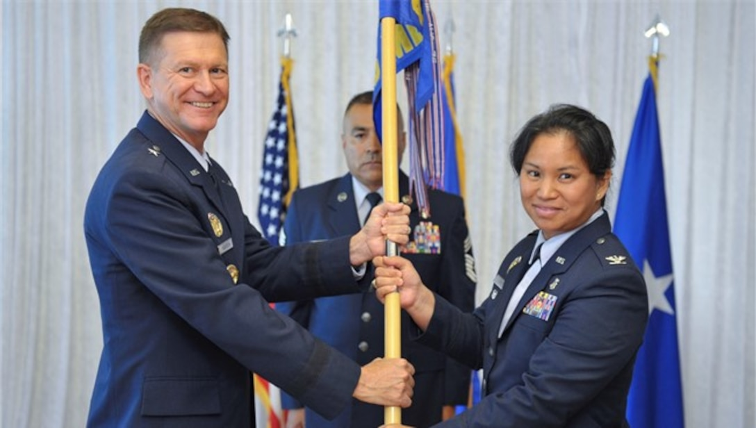Brigadier General Wayne Monteith presents Colonel Gigi Simko with guidon for change of command ceremony for the 45th Space Wing Medical Group.