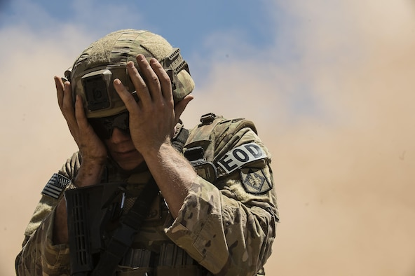 Airman 1st Class Jared Ball, EOD team member, shields his face from oncoming sand during fly-away training at the Florence Military Reservation in Florence, Ariz., July 21, 2017. The wind gusts caused from the Black Hawks take-off and landing kick up sand from the desert floor causing low visibility. (U.S. Air Force photo/Airman 1st Class Alexander Cook)