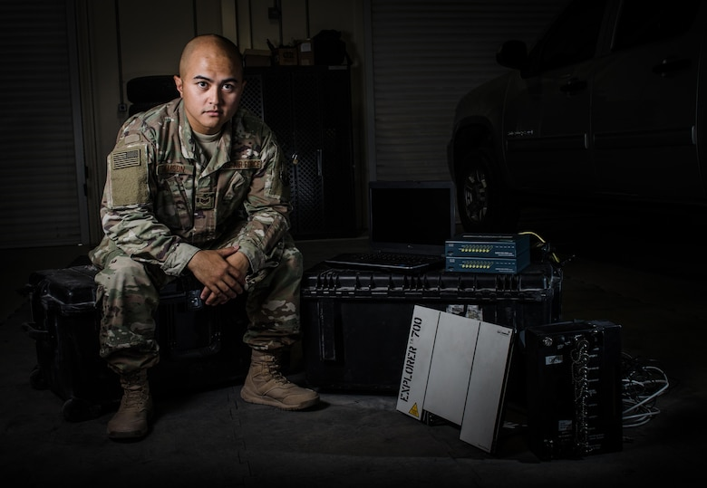 U.S. Air Force Staff Sgt. Junbryan Samson, a cyber network technician assigned to the U.S. Air Forces Central Command communications division at the Combined Air Operations Center sits next to a communications fly-away kit July 31, 2017, at Al Udeid Air Base, Qatar. Samson's maintains and administers the CFK, which allows Airmen to establish crucial internet and voice links with bare-base resources anywhere in the world via wireless routers, very small aperture terminal satellite and broadband global area network satellite link (U.S. Air Force photo by Staff Sgt. Alexander W. Riedel)