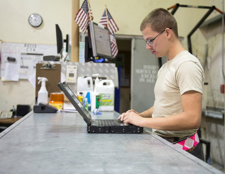 U.S Air Force Airman 1st Class Cody Maddux, a guidance and control technician with the 763rd Expeditionary Aircraft Maintenance Unit, prepares a computer with all the required RC-135V/W Rivet Joint checklist at Al Udeid Air Base, Qatar, July 27, 2017.