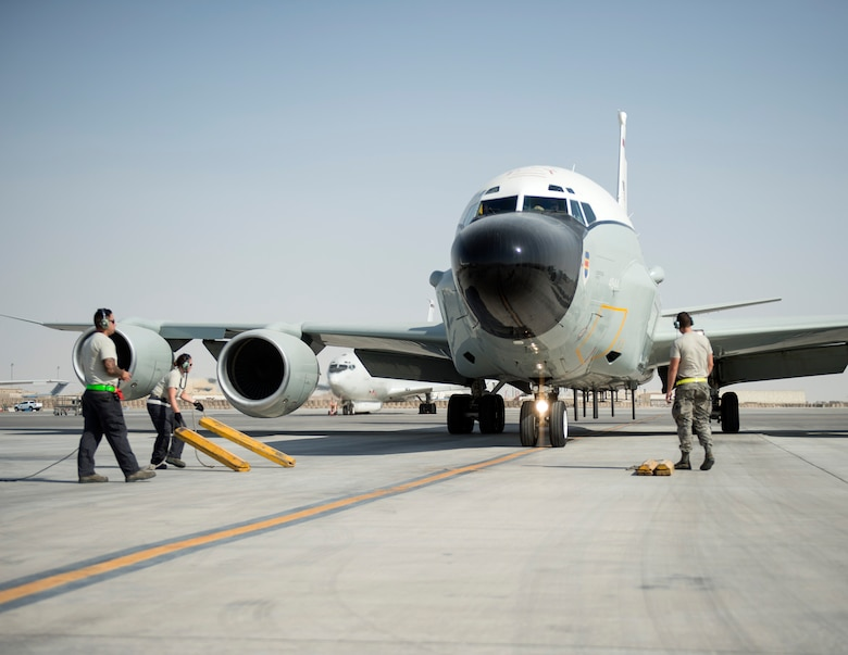 U.S Air Force Airmen with the 763rd Expeditionary Aircraft Maintenance Unit, prepare to place chocks for RC-135V/W Rivet Joint at Al Udeid Air Base, Qatar, July 27, 2017.