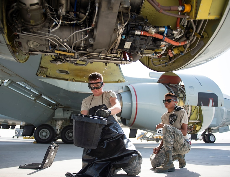 U.S Air Force Airman 1st Class Gregory Tjernlund, left, an aircraft propulsion system technician and Airman 1st Class Raven Quiles, an electrical and environmental technician with 763rd Expeditionary Aircraft Maintenance Unit, perform routine engine maintenance at Al Udeid Air Base, Qatar, July 27, 2017.