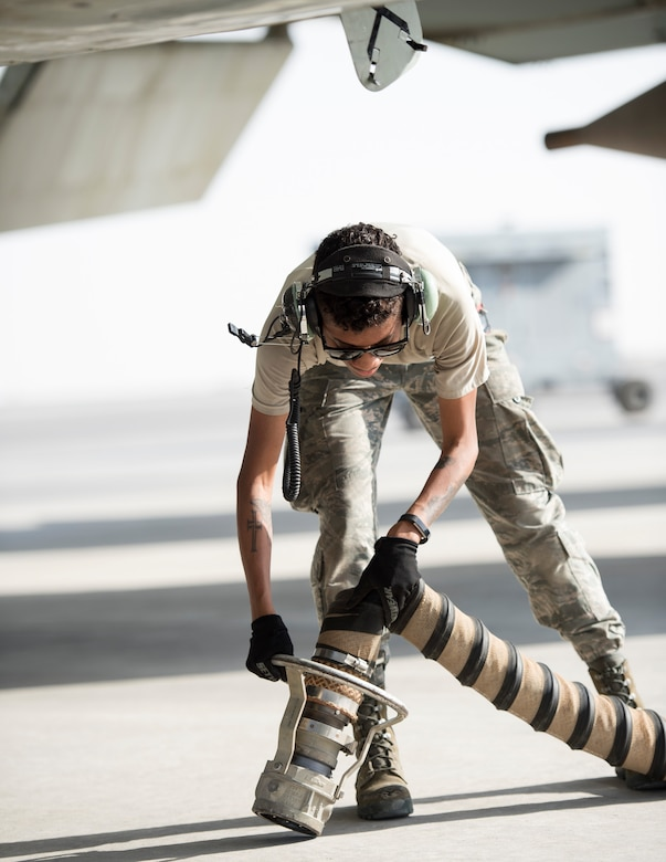 U.S Air Force Airman 1st Class Raven Quiles, an electrical and environmental technician with the 763rd Expeditionary Aircraft Maintenance Unit, prepares to attach the A/M32A-60B Generator Set to a RC-135V/W Rivet Joint at Al Udeid Air Base, Qatar, July 27, 2017.