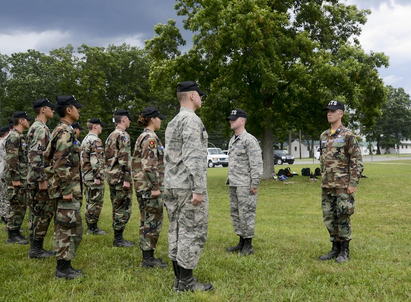 Air Force Airmen 1st Class Shawn and Kevin Utermohlen inspect a Civil Air Patrol cadet formation.