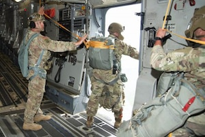 Soldiers prepare to jump from an aircraft.