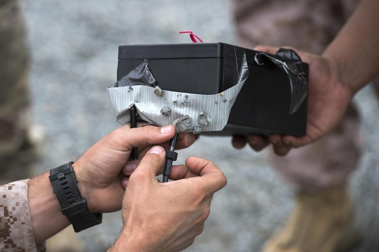 A service member takes apart a fake bomb.