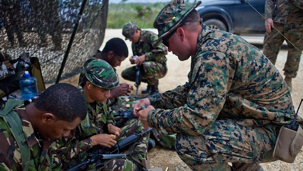 U.S. Marine Sgt. Dustin J. Houghton, an infantry trainer with the Belize Detachment, Ground Combat Element, Special Purpose Marine Air-Ground Task Force - Southern Command, shows service members with the Belize Defence Force how to load their ammunition into magazines as part of basic combat marksmanship training near Ladyville, Belize, July 20, 2017. The training was part of basic infantry skills course taught by the detachment to members of the BDF. The Marines and sailors of SPMAGTF-SC are deployed to Central America for the next six months to conduct security cooperation training and engineering projects with their counterparts in Honduras, Guatemala, Belize and El Salvador.