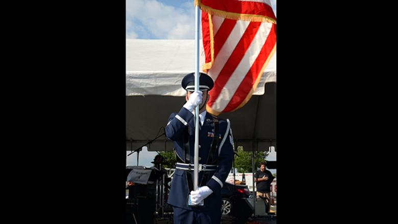Air Force Tech. Sgt. Jonathan D. Kane, a 177th Fighter Wing Honor Guard Member, displays the colors during Hamilton Township's National Night Out at the Hamilton Mall in Mays Landing, New Jersey, on Aug. 1, 2017.