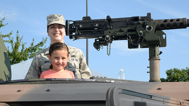 Air Force Senior Airman Kelly A. Grau, a member of the 177th Fighter Wing's Security Forces Squadron, poses for a photo with a community member during Hamilton Township's National Night Out at the Hamilton Mall in Mays Landing, New Jersey, on Aug. 1, 2017.