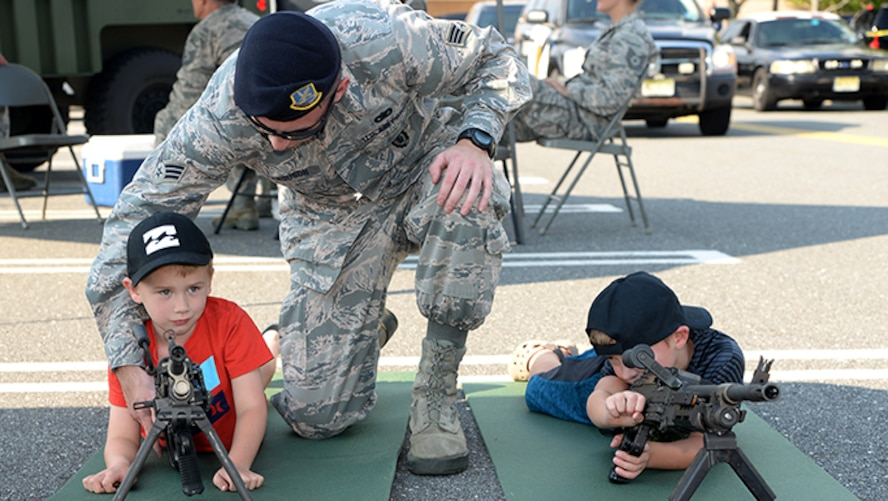 Air Force Senior Airman Zachary D. Ferguson, a member of the 177th Fighter Wing's Security Forces Squadron, shows a community member how to use security forces equipment during Hamilton Township's National Night Out at the Hamilton Mall in Mays Landing, New Jersey, on Aug. 1, 2017.