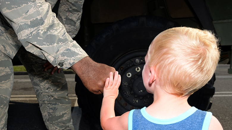 Air Force Staff Sgt. John D. Lundy, a member of the 177th Fighter Wing's Security Forces Squadron, fist bumps with a community members during Hamilton Township's National Night Out at the Hamilton Mall in Mays Landing, New Jersey, on Aug. 1, 2017.