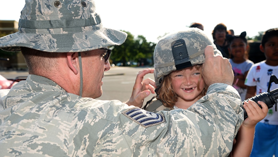 Air Force Tech. Sgt. Keith M. Curtis, a member of the 177th Fighter Wing's Security Forces Squadron, helps a community member don a security forces helmet during Hamilton Township's National Night Out at the Hamilton Mall in Mays Landing, New Jersey, on Aug. 1, 2017.