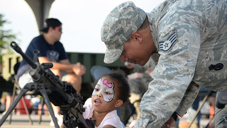 Staff Sgt. Richard A. Elliot, a member of the 177th Fighter Wing's Security Forces Squadron, shows a community member how to use security forces equipment during Hamilton Township's National Night Out at the Hamilton Mall in Mays Landing, New Jersey, on Aug. 1, 2017.