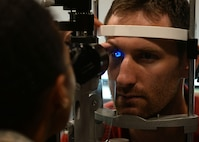 Capt. Brennan Schilperoort, 41st Airlift Squadron pilot, has his eye inspected by Maj. Felicia Rinken, 19th Medical Group optometrist, July 24, 2017 at the 19th Medical Group optometry clinic on Little Rock Air Force Base, Arkansas. The optometry clinic ensures Airmen at Little Rock Air Force base are visually fit to fight by providing annual eye exams, pre-operation and post operation eye care, and diagnosing and treating eye infections. (U.S. Air Force photo by Airman 1st Class Codie Collins)