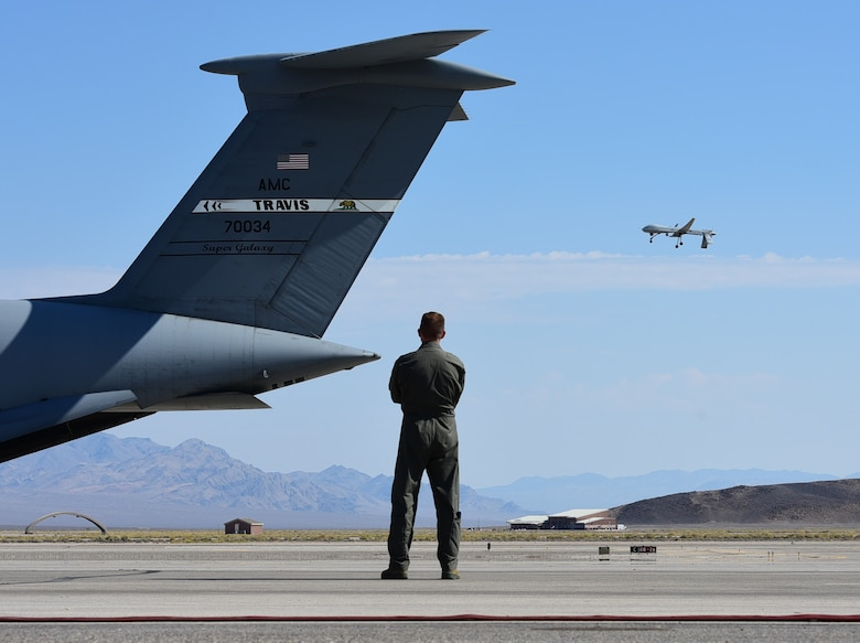 Maj. Richard, 432nd Wing MQ-1 Predator pilot, watches the Predator fly over a C-5M Supergalaxy while reminiscing how about how he became a U.S. Air Force pilot. As a seven-year-old boy, Richard fell in love with the C-5 and aviation during Lethbridge International Airshow in Alberta, Canada. More than twenty years later he became a C-5 pilot, flying for four years in that airframe. Now, he flies the MQ-1 Predator. (U.S. Air Force photo/Senior Airman Christian Clausen)