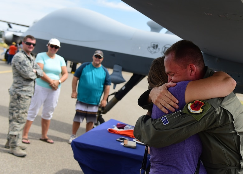 Maj. Richard, 432nd Wing MQ-1 Predator pilot, hugs his cousin July 15, 2017, at the Lethbridge International Airshow in Alberta, Canada. Richard grew up with his cousin in Lethbridge for 15 years hasn't seen her since moving to the United States. Richard was able to reconnect with family and friends in his hometown while in town showcasing the MQ-9 Reaper and its capabilities. (U.S. Air Force photo/Senior Airman Christian Clausen)