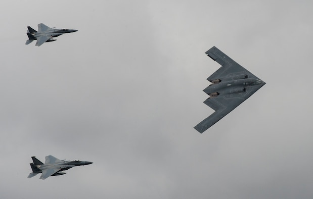 A U.S. Air Force B-2 Spirit Bomber and two F-15 Strike Eagle aircraft fly past spectators