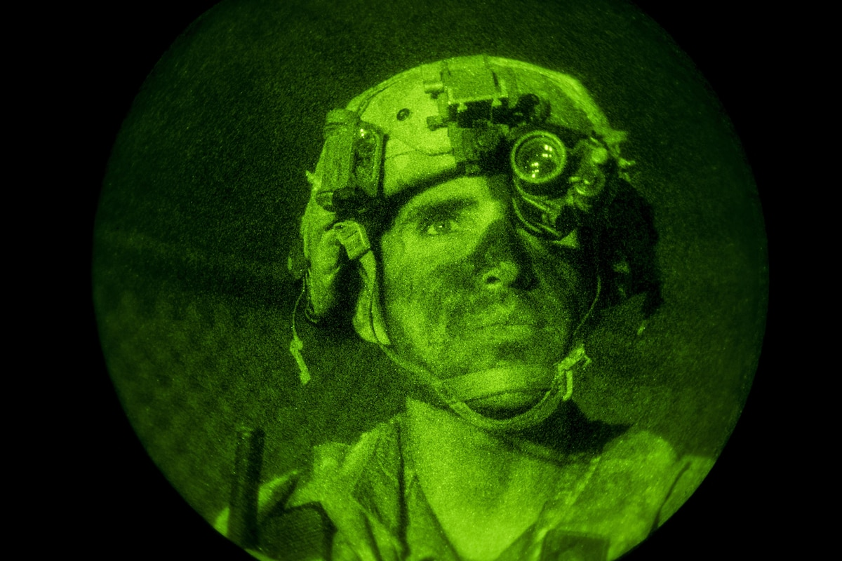 A soldier in a green light watching troops at night.