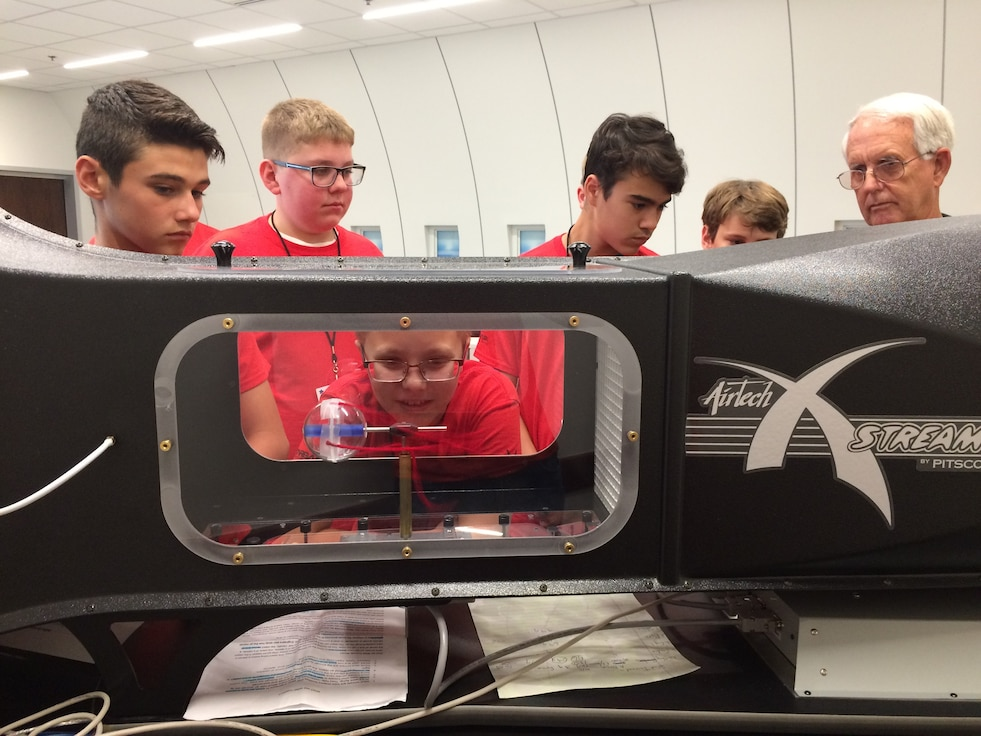 Students looking in wind tunnel.