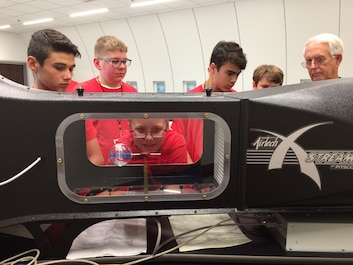 Picture of five boys looking into a wind tunnel with an instructor.