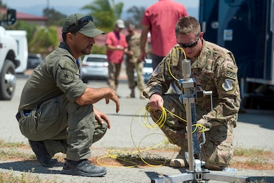 Air Force Staff Sgt. Brandon Ulmer, left, and Merl Mireles, an investigator with Orange County Sherriff's Department in California, prepare a controlled small blast firing device during the Raven's Challenge explosive ordnance disposal exercise at Camp Pendleton, Calif., Aug. 1, 2017. Raven's Challenge is an Army-funded exercise led by the Bureau of Alcohol, Tobacco, Firearms, and Explosives with support and participations from multiple federal, state and local agencies. DoD photo by EJ Hersom