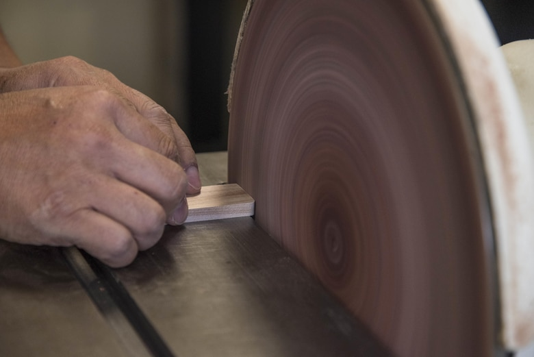 Yutaka Kashiwazaki, a 35th Force Support Squadron woodshop master laborer, uses a circular sander to smooth a detail wood piece in the woodshop at Misawa Air Base, Japan, Aug. 1, 2017. Kashiwazaki has more than 30 years of experience in woodworking and teaches others how to properly determine and use power tools for their projects. (U.S. Air Force Airman 1st Class Sadie Colbert)