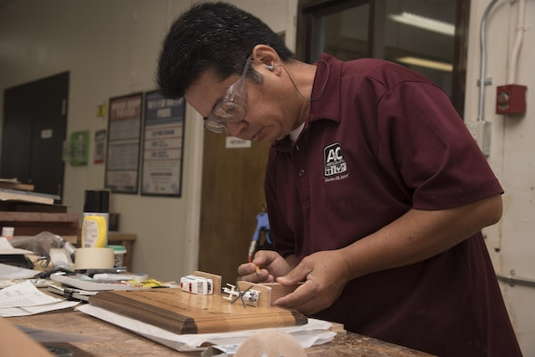 Yutaka Kashiwazaki, a 35th Force Support Squadron woodshop master laborer, adds details to a plaque at the woodshop at Misawa Air Base, Japan, Aug. 1, 2017. Vanessa Breen, the 35th FSS director of arts and crafts and auto complex, considers Kashiwazaki an important asset to the shop because of his talent and skill in woodworking. (U.S. Air Force photo by Airman 1st Class Sadie Colbert)